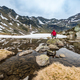 Hiker sits on rock near lake in Andorra - PhotoDune Item for Sale