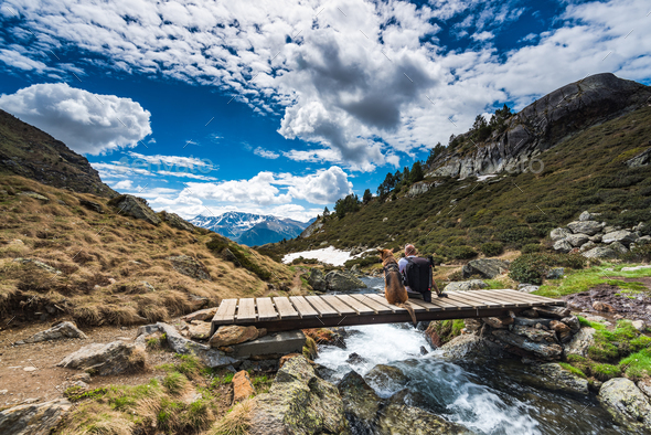 Wanderluster hiker sitting with dog in mountains - Stock Photo - Images