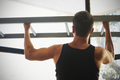 Athlete muscular fitness male model pulling up on horizontal bar