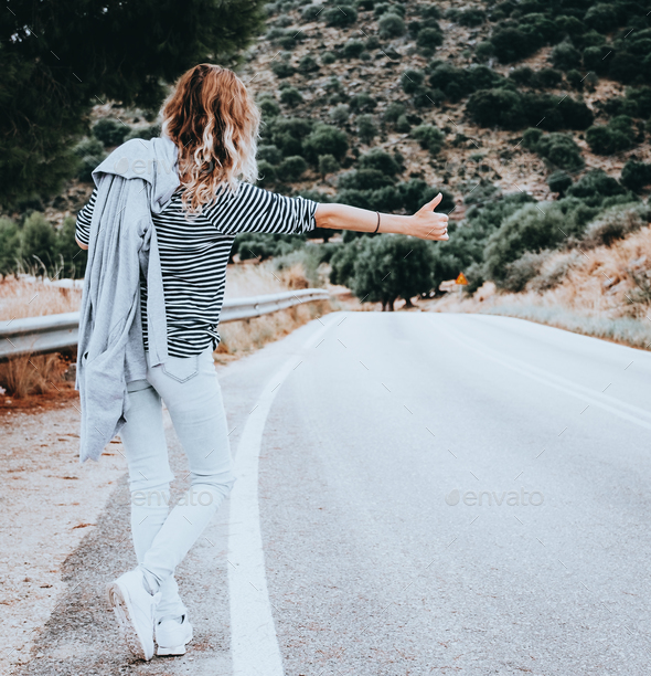 Woman hitchhiking along the road. - Stock Photo - Images