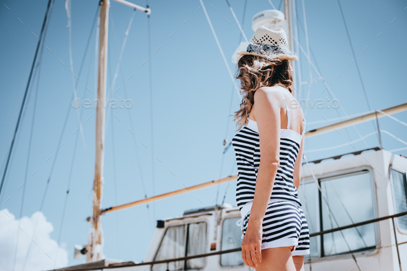 Woman in striped clothes standing near yacht in sunny summer day. - Stock Photo - Images