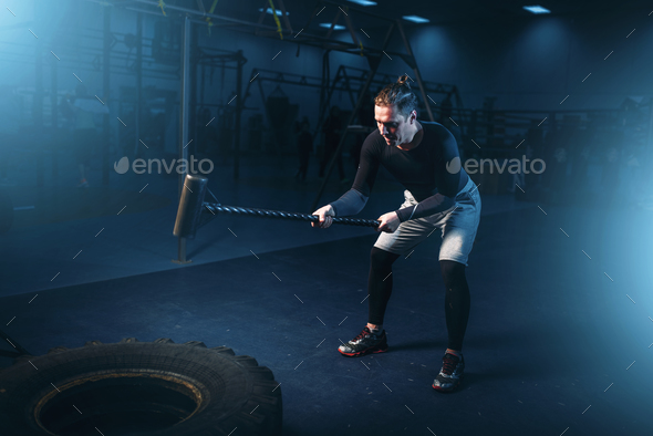 Training in gym, man with sledgehammer hits tire - Stock Photo - Images