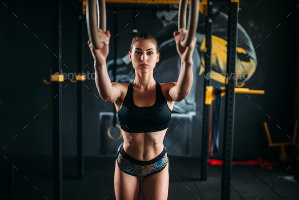 Slim female athlete training on gymnastic rings - Stock Photo - Images