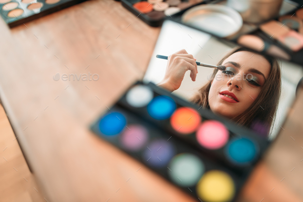 Woman sitting against mirror in beauty studio - Stock Photo - Images