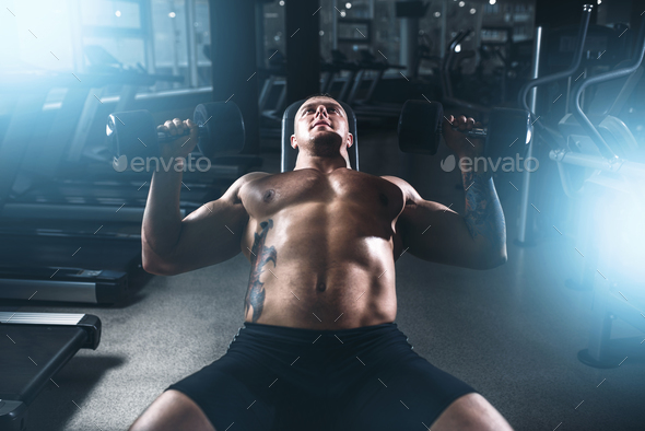 Male bodybuilder training with dumbbells in gym - Stock Photo - Images