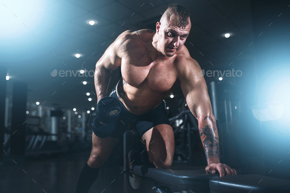 Athlete with muscular body lifting dumbbells - Stock Photo - Images