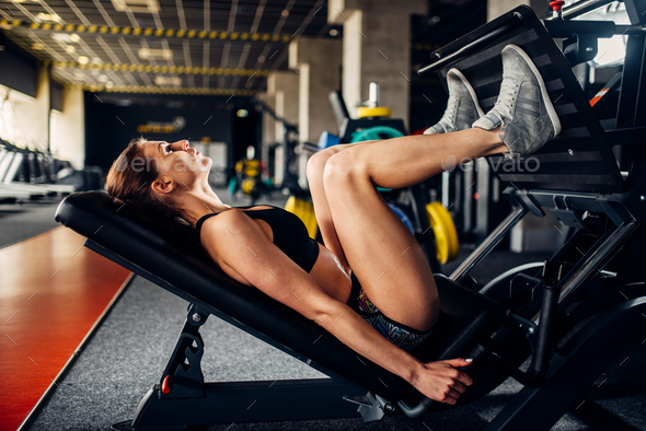 Woman in sportswear trains on exercise machine - Stock Photo - Images