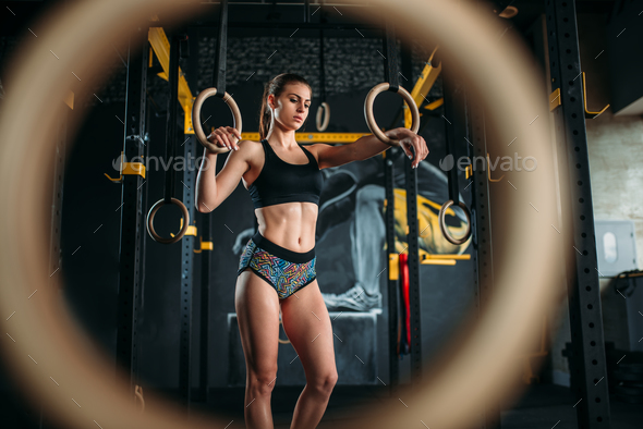 Slim female athlete exercise on gymnastic rings - Stock Photo - Images