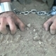 Prisoner in Chains on His Knees Touching the Dusty Ground