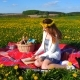 Young Beautiful Woman on a Picnic, Reading a Book on a Field of Yellow Flowers.
