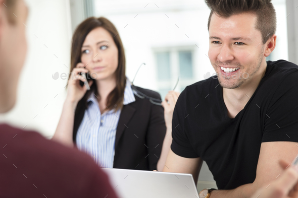 Young Businessman Smiling While Looking At Colleague - Stock Photo - Images