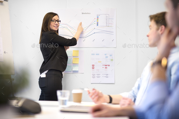 Female Professional Explaining Graph To Male Executives - Stock Photo - Images