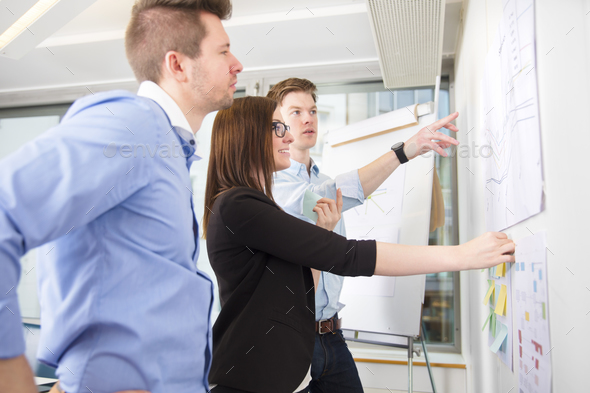 Business People Discussing Over Line Graph Stuck On Wall - Stock Photo - Images