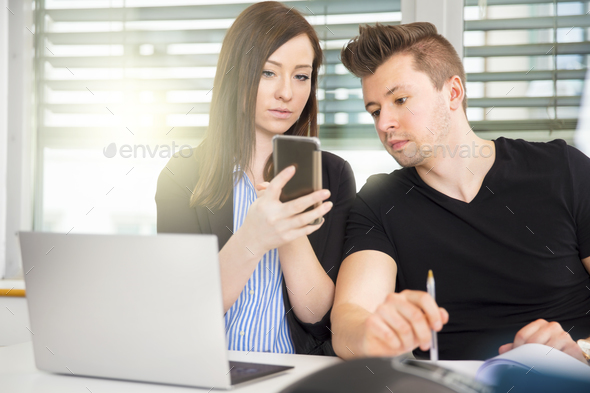 Business People Using Smart Phone At Desk In Office - Stock Photo - Images