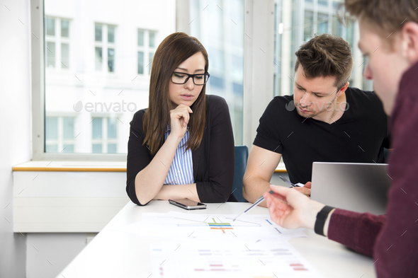 Business People Discussing Over Chart At Desk - Stock Photo - Images