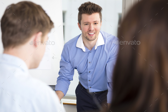 Businessman Smiling While Looking At Colleagues In Office - Stock Photo - Images