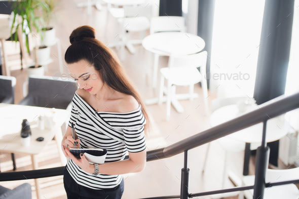 Picture of adult beautiful woman standing in a cafe and making notes while looking at the notebook. - Stock Photo - Images
