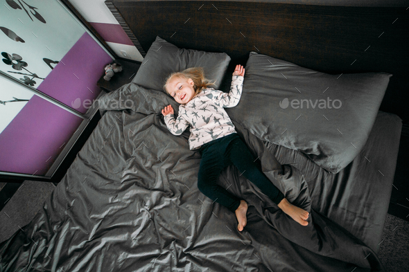 Cute happy little girl in pajama in the morning - Stock Photo - Images