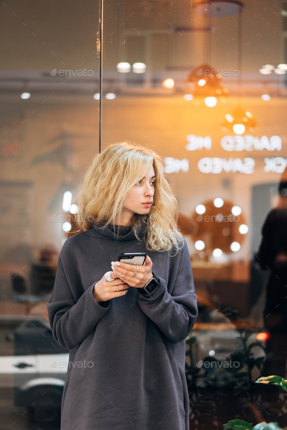 Blonde girl standing with smartphone - Stock Photo - Images