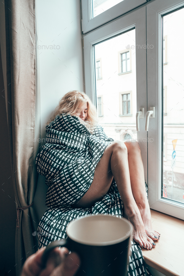 girl sitting on a window in a blanket - Stock Photo - Images