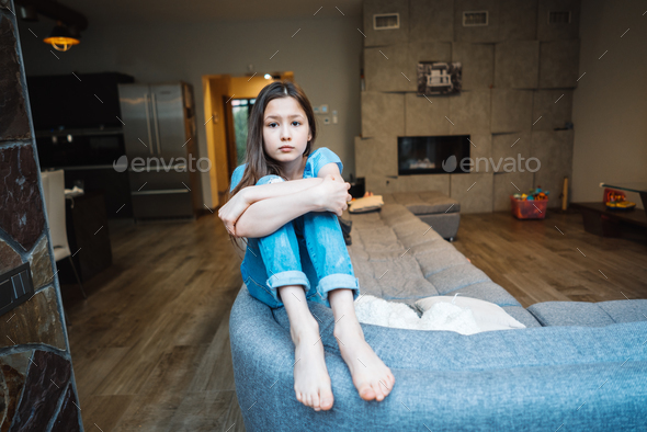 Positive smiling teenage girl on a couch. - Stock Photo - Images