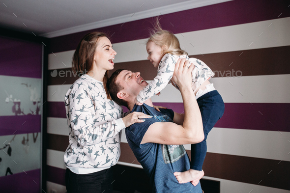 Mom, Dad and little girl having fun together - Stock Photo - Images