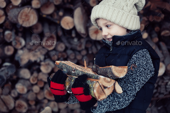 Little boy chopping firewood in the front yard at the day time. - Stock Photo - Images