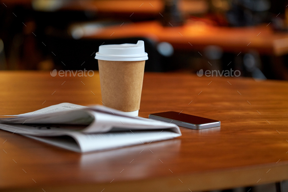 coffee cup, smartphone and newspaper on cafe table - Stock Photo - Images