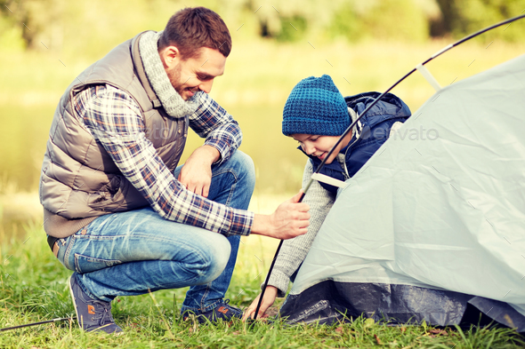 happy father and son setting up tent outdoors - Stock Photo - Images