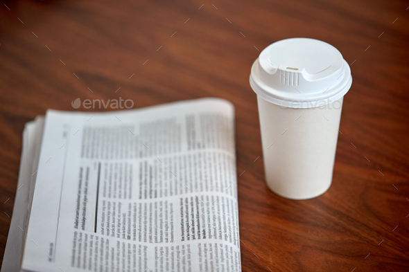 coffee drink in paper cup and newspaper on table - Stock Photo - Images