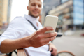close up of man texting on smartphone in city - PhotoDune Item for Sale