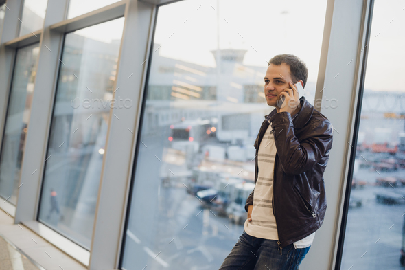 Businessman talking on the phone at airport terminal - Stock Photo - Images