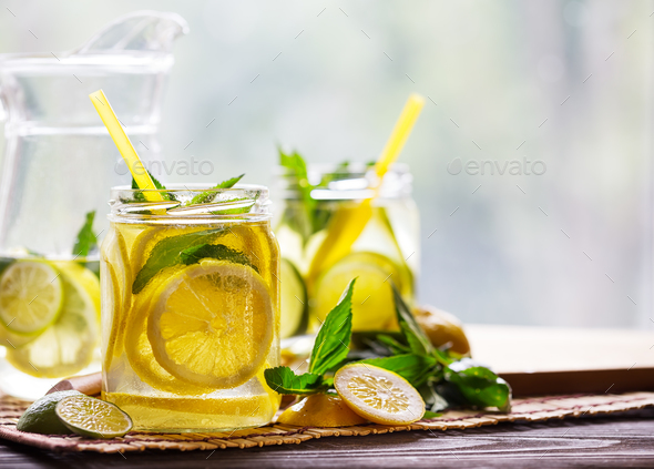 Banks and a jug with cold lemonade and ingredients on a wooden t - Stock Photo - Images