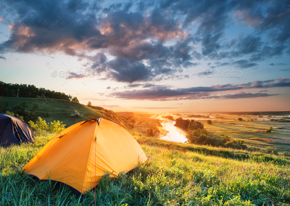 Orange tent on a hill above the river - Stock Photo - Images