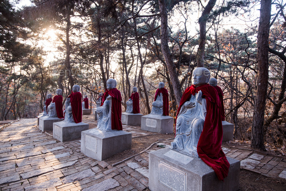Stone Monk Statues wearing mantles at chinese forest - Stock Photo - Images