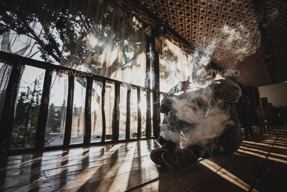 vaping young man produces vapor on sunset silhouette - Stock Photo - Images