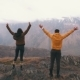 Young Couple of Travelers Raise Arms in the Background of Mountains