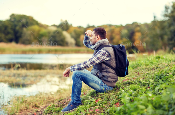 smiling man with backpack resting on river bank - Stock Photo - Images