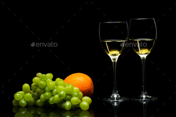 Glasses for wine, grapes and oranges on a black background - Stock Photo - Images