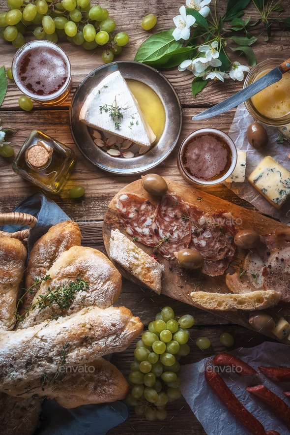 Homemade baguette, cheese, olives, grapes, flowers on old boards - Stock Photo - Images
