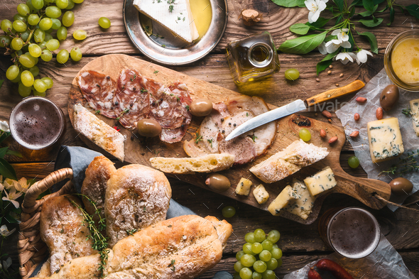 Homemade bread, cheese, olives, grapes, flowers on old boards - Stock Photo - Images