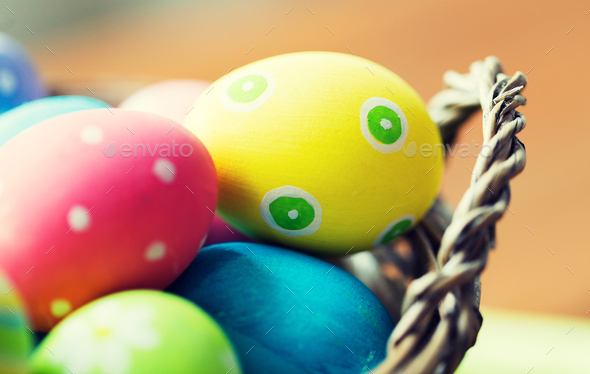 close up of colored easter eggs in basket - Stock Photo - Images