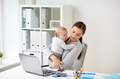 businesswoman with baby and smartphone at office