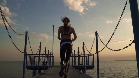 Girl Athlete with a Beautiful Figure Runs on the Pier of the Sea. Sportswoman Finishes the Workout