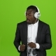 Businessman and Headphones on Ears, Listening To Music and Dancing on the Spot. Green Screen