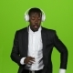 African American Man Dances Motion Latin and Listens To Music in the Earphones. Green Screen