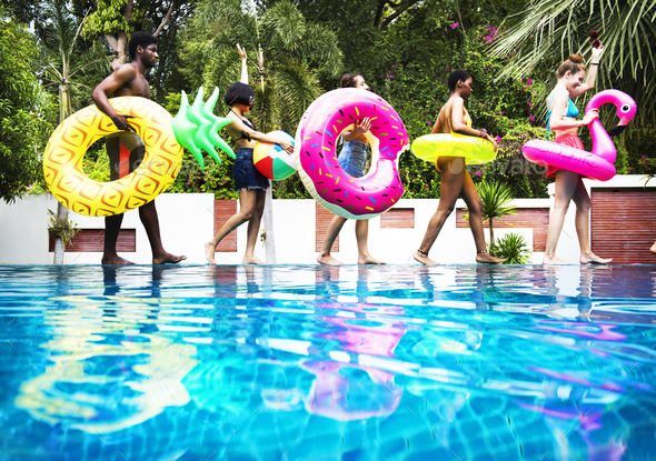 Group of diverse friends enjoying summer time by the pool with i - Stock Photo - Images