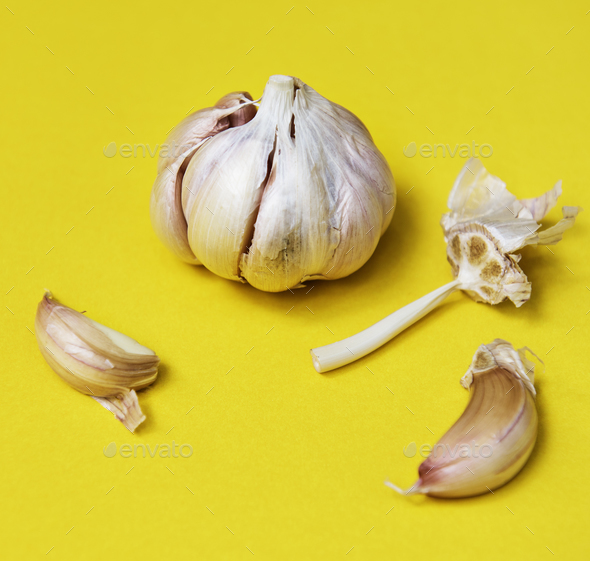 Closeup of garlic cloves on yellow background - Stock Photo - Images