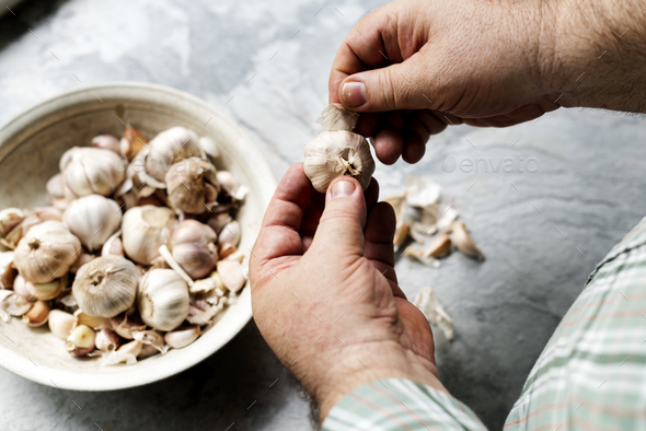 Closeup of hand peeling garlic - Stock Photo - Images
