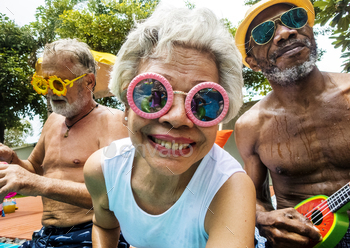 Closeup of diverse senior adults sitting by the pool enjoying su